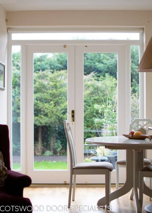 White painted wooden glazed french door with sidelight frame. Double glazed clear glass and brass hardware
