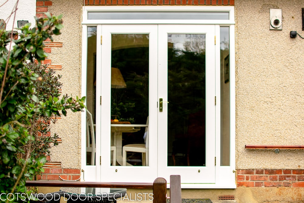 White painted wooden glazed french door with sidelight frame. Double glazed clear glass and brass hardware. Doors opening into garden