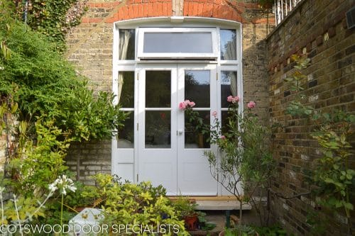 Victorian French door with sidelight door frame. Opening window above the pair of french doors. Detailed simple wooden glazing bar diving glass panes. All painted white