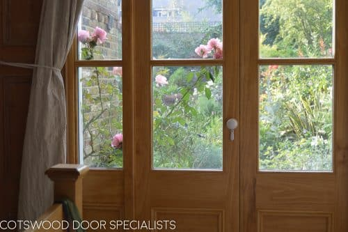 Victorian French door with sidelight door frame. Opening window above the pair of french doors. Detailed simple wooden glazing bar diving glass panes. Interior shot with light shining in. Natural wooden finish on Accoya with beautiful grain