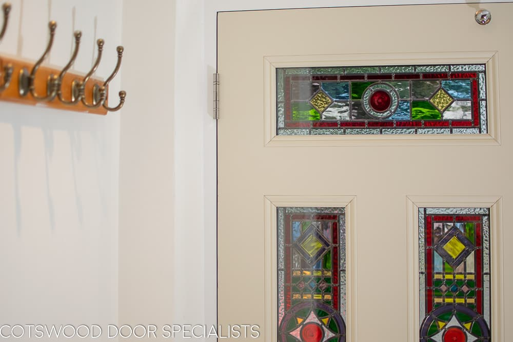 Victorian hallway with coat hooks and stained glass front doors