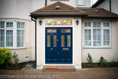 Victorian double doors with stained and leaded glass. Doors are painted dark blue with Teknos spray paint, finish is beautiful. Intricate stained glass design to the doors and the frame. The new door frame has the number above the doors incorporated in the stained glass.