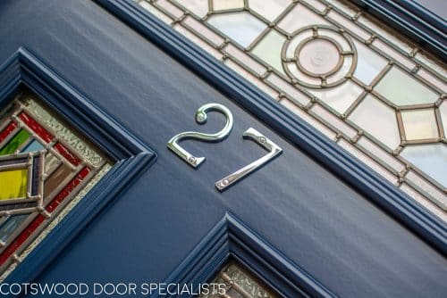 Victorian double doors with stained and leaded glass. Doors are painted dark blue with Teknos spray paint, finish is beautiful. Intricate stained glass design to the doors and the frame. The new door frame has the number above the doors incorporated in the stained glass. closeup of polished chrome door numbers