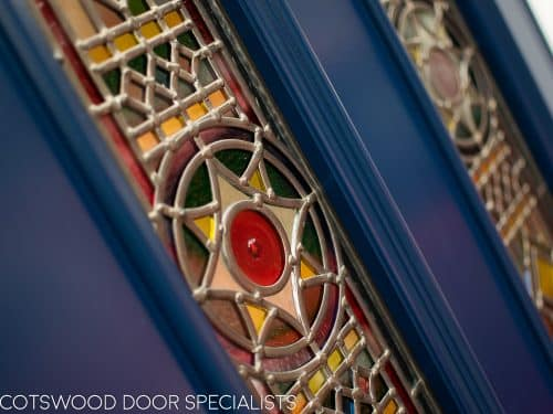 Victorian double doors with stained and leaded glass. Doors are painted dark blue with Teknos spray paint, finish is beautiful. Intricate stained glass design to the doors and the frame. The new door frame has the number above the doors incorporated in the stained glass. closeup of stained glass