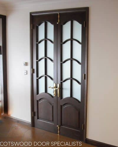 Tall glazed internal doors, arched glass with glazing bars, dark wood stain, arched obscure glass, polished brass furniture