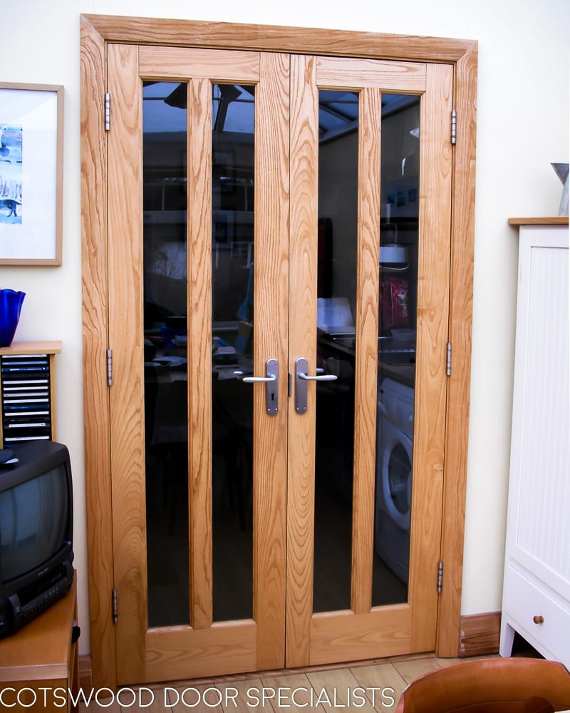 Bespoke glazed internal doors and frame, tall clear glass panels, light wood stain, satin chrome furniture, pair of internal double doors