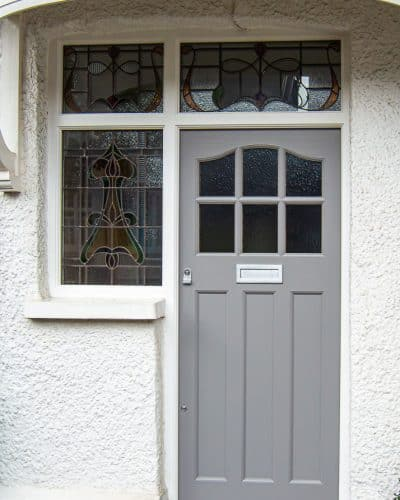 1930's External front door with sidelight door frame. Wooden door with six obscure glass panes. Door frame has three stained glass panes. Door painted grey and frame painted white. Satin chrome door furniture. Shot showing canopy. This door has an elegant curve at the head of the door, six glazing apertures and three flat panels.
