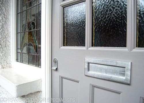 1930's External front door with sidelight door frame. Wooden door with six obscure glass panes. Door frame has three stained glass panes. Door painted grey and frame painted white. Satin chrome door furniture. Closeup of door detail