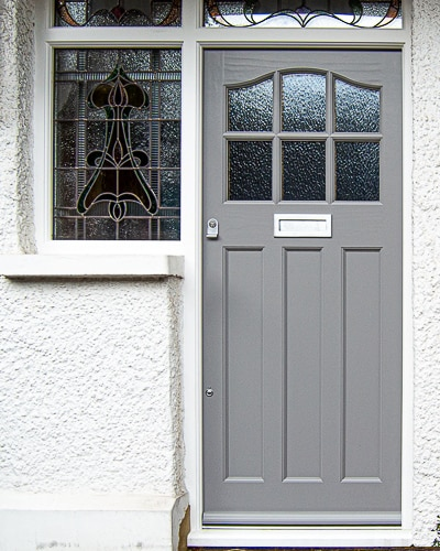 1930's External front door with sidelight door frame. Wooden door with six obscure glass panes. Door frame has three stained glass panes. Door painted grey and frame painted white. Satin chrome door furniture. This door has an elegant curve at the head of the door, six glazing apertures and three flat panels.