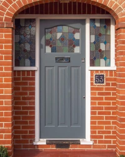 1930s style stained glass door. Front door painted light grey with a white door frame. London house with red brickwork. Wooden door. Leaded glass with different colours. Polished chrome door furniture.