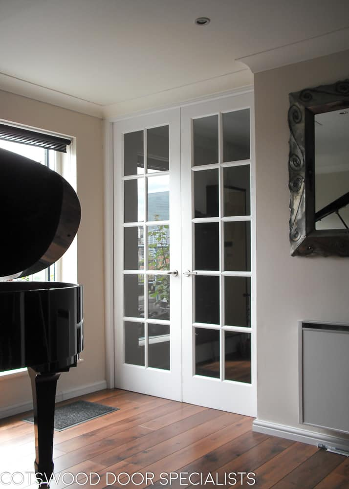 Georgian glazed internal doors with door frame. Extra tall doors painted white with clear glass. Double doors with narrow glazing bar. Light shining on doors in room with grand piano