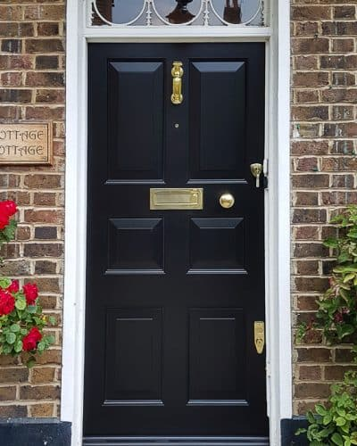 Georgian raised panelled door with fanlight painted black. polished brass furniture. fitted in London into existing frame. decorative Georgian fanlight with metal glazing.