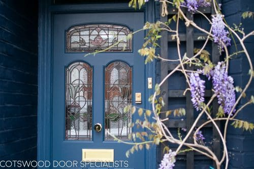 Stained Glass Victorian door fitted into classic London terraced house. Three arched top stained glass panels and three wooden panels. Special gold leaf number above door. Door, frame and house painted blue in farrow and ball colours. Wisteria growing around front door. Polished brass door furniture including letterbox and knob