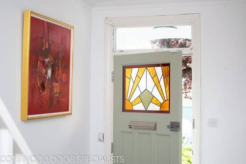 Stained glass 1930's Door. Stained glass with a geometric art deco pattern. Different colours of glass combined with different textures highlight the design. Door painted light green in colour. Satin chrome door fittings Hallway view with light shining though the stained glass
