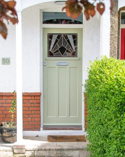 Stained glass 1930's Door. Stained glass with a geometric art deco pattern. Different colours of glass combined with different textures highlight the design. Door painted light green in colour. Satin chrome door fittings. Wooden door frame has a clear piece of glass.