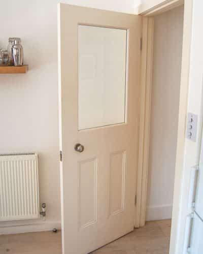 Glazed Victorian internal door. Around half glass letting light shine into the hallway. Bespoke wooden internal door, with two flat panels in the lower section. Period panel mouldings to the door panels. Antique brass door knobs. Shot from the kitchen.