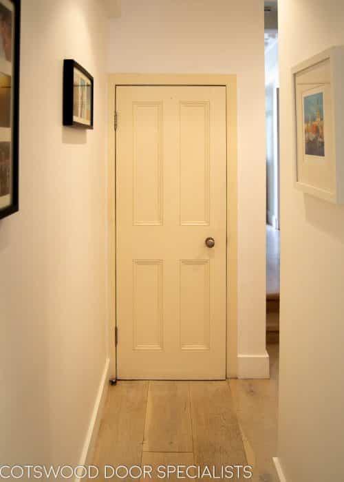 Victorian internal door. Bespoke four panelled door made with period panel moulding. Door installed in a London home. Painted finish. Antique brass door knob. View form hallway