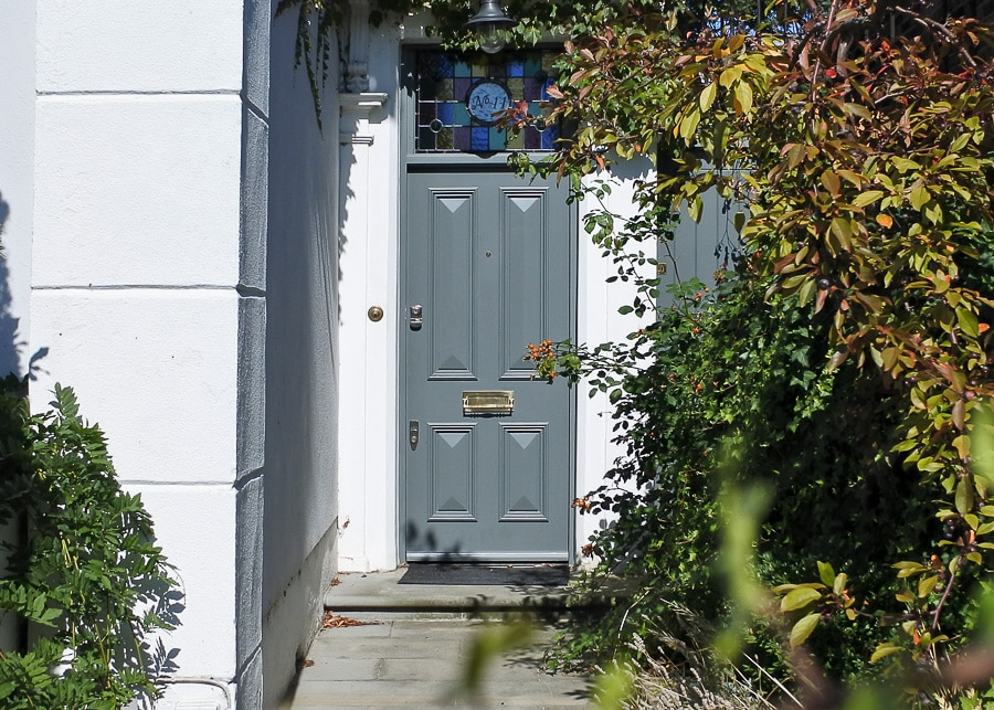 four panelled door fitted into a late Georgian London house. Door and frame painted a light green/ grey colour. Stained glass fitted above the door.
