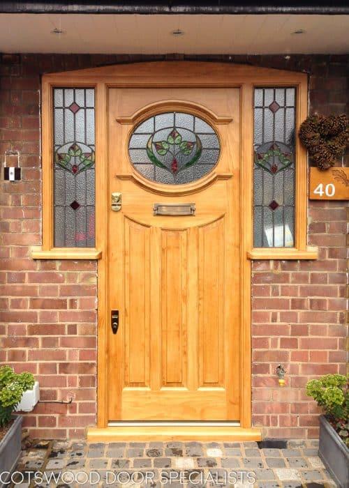 natural wooden 1930s door with stained glass. Door and sidelight door frame in light oak coloured accoya wood. Stained glass to door and also door frame. Antique brass door furniture. Secure traditional door locks