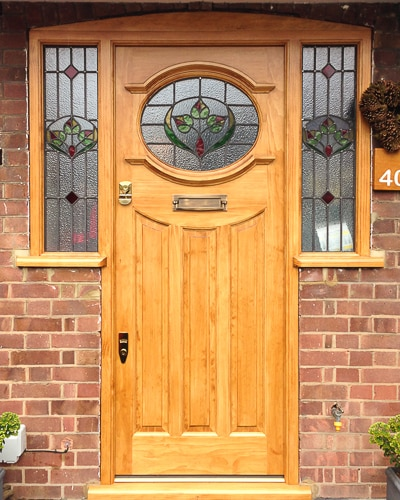 natural wooden 1930s door with stained glass. Door and sidelight door frame in light oak coloured accoya wood. Stained glass to door and also door frame. Antique brass door furniture. Secure traditional door locks
