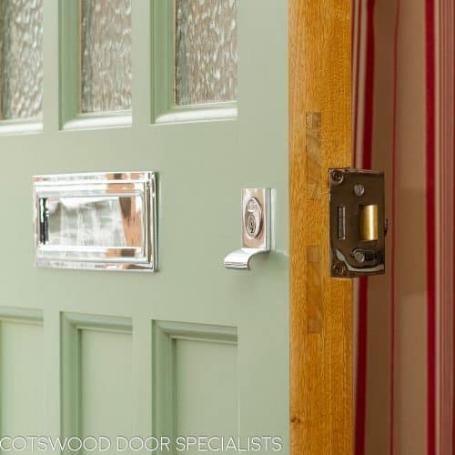 Green 1930s front door with textured obscure glass. Door made in accoya, with new accoya door frame. Satin chrome door furniture. Closeup shot of door lock and letterbox