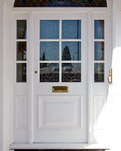 Large Edwardian front and sidelight arched frame painted white. Door has stained and textured glass. Red brick door arch surrounding the door. Polished brass door furniture