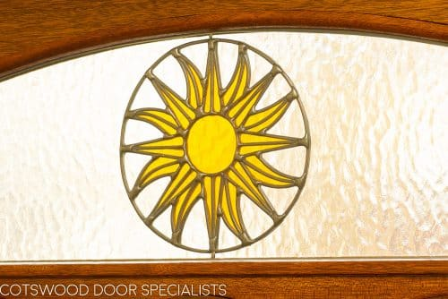 stained timber Edwardian front door. Edwardian design stained glass including a sun pattern. Polished brass door furniture. Door fitted into an existing painted white door frame surrounded by red brickwork. Closeup of stained glass sun