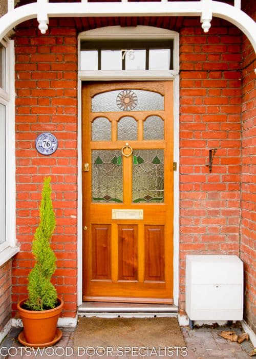 stained timber Edwardian front door. Edwardian design stained glass including a sun pattern. Polished brass door furniture. Door fitted into an existing painted white door frame surrounded by red brickwork