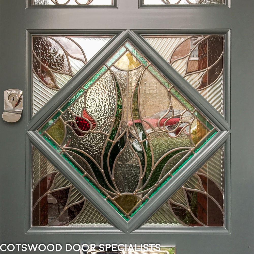 Edwardian front door painted slate grey with diamond stained glass and polished chrome furniture fitted into existing frame in London. Close up of Edwardian decorative stained glass