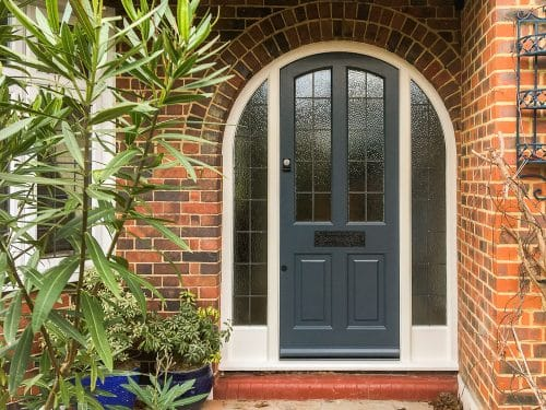 4 panel arched 1930's door, painted grey, with frame and sidelights, obscure glass with leaded oblongs, black iron furniture, fitted by our carpenters in London