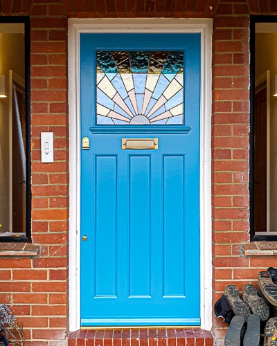 Art Deco front door painted bright blue. Art deco sunrise stained coloured glass. Antique brass door furniture. Fitted into an existing door frame in London