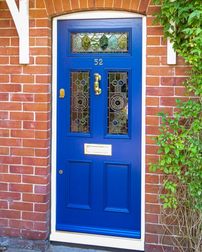 Dark blue Edwardian door with stained glass fitted into open porch. Door has beautiful leaded light glass in a geometric design. Polished brass letterplate, door knob and door furniture.