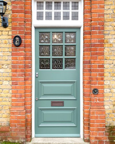Edwardian style front door with bullion leaded glass. Decorative 9 pane Edwardian style front door fitted into a wooden frame in London. Paint finish in green with a white door frame. Door made in Accoya wood.