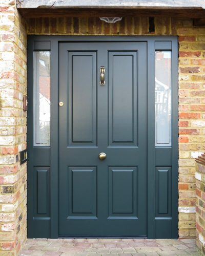 Raised panelled solid Victorian front door and new frame. Bespoke traditional door fitted into an open porch surrounded by oak beams. New door is painted dark green and the frame is also dark green. High security multi point locking system. Antique brass door furniture fitted with a Doctor knocker and a door knob