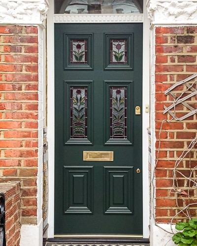 Stained glass Georgian front door fitted in London. Decorative door frame with dental block to transom. Original stained glass design with flowers. Door painted dark green with brass door furniture