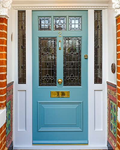 Victorian external door fitted with a new decorative door frame. Traditional stained glass made as double glazed units. Painted door and frame. Door furniture. Wide Victorian open porch with Victorian style tiles